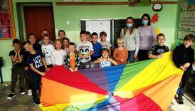 Dzieci i wychowawcy pozują do zdjęcia, trzymają przed sobą chustę Klanza