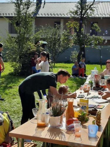 Uczestnicy pikniku w ogrodzie, w tle bańki mydlane