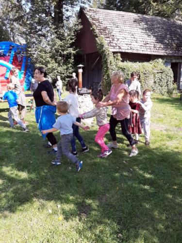 Uczestnicy pikniku podczas zabawy ruchowej w ogrodzie