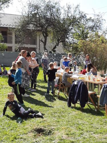 Uczestnicy pikniku wokół stołu, wokół nich bańki mydlane