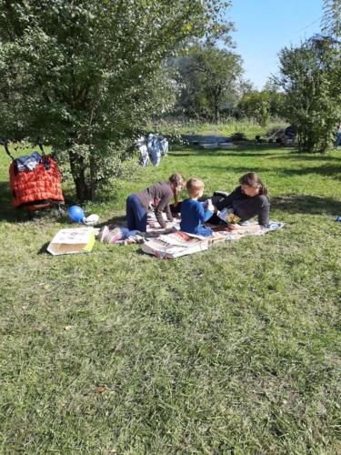 Uczestnicy pikniku siedzą na kocu w ogrodzie