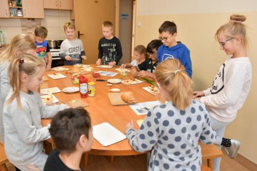 Dzieci zebrane wokół stołu robią kanapki