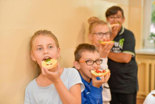Dzieci jedzą wykonane przez siebie kanapki