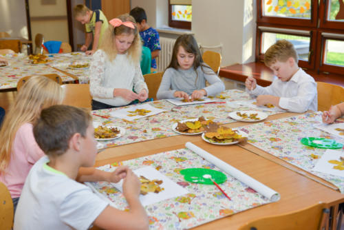 Dzieci wykonują prace plastyczne z wykorzystaniem jesiennych liści