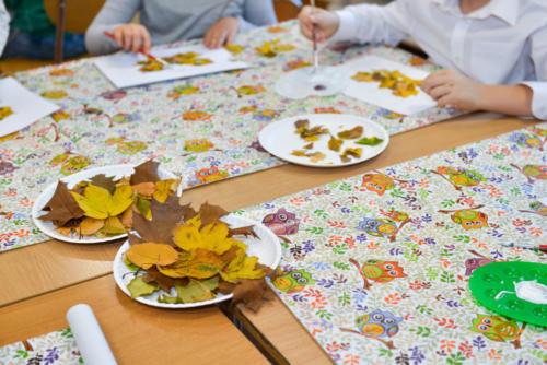Jesienne, kolorowe liście leżą na talerzykach na stole