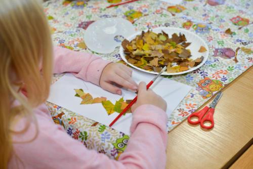 Dziewczynka przykleja fragmenty liści do kartki papieru
