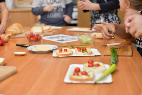Ręce dzieci, które robią kolorowe kanapki