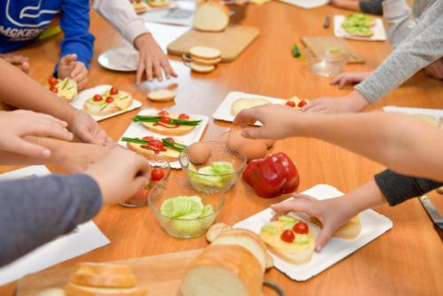Ręce dzieci, które sięgają po produkty potrzebne do zrobienia kanapek, m.in. plasterki ogórka, pomidorki koktajlowe, paprykę i jajka.
