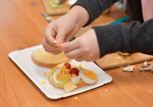 Zbliżenie na ręce dziecka, które ozdabia kanapkę jajkiem i pomidorkami