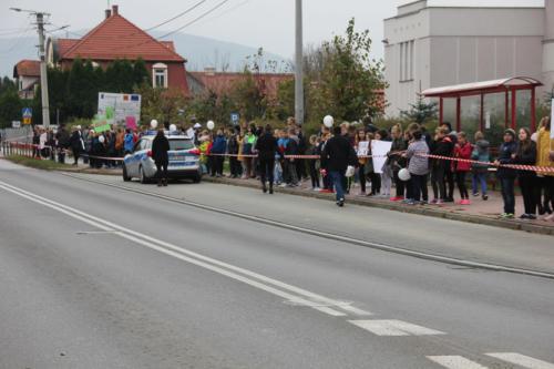 Droga, przy niej stoją dzieci oddzielone od ulicy taśmą
