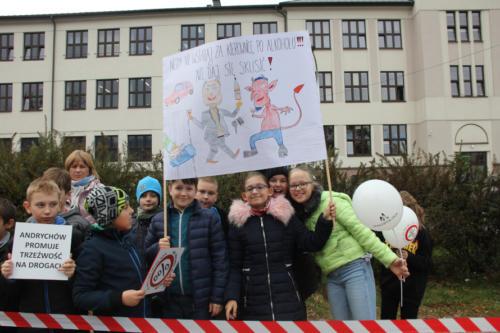 """Dzieci z plakatem przedstawiającym człowieka kuszonego przez diabła i napisem """"Nie wsiadaj za kierownicę po alkoholu! Nie daj się skusić"""""""