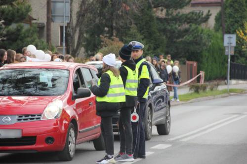 Dzieci wręczają kierowcy ulotki promujące trzeźwość na drogach