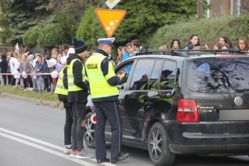 Policjant sprawdza trzeźwość kierowcy, obok dzieci w kamizelkach odblaskowych