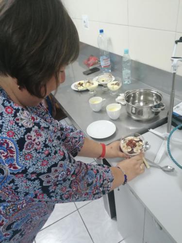 Kobieta przygotowuje deser w pucharkach