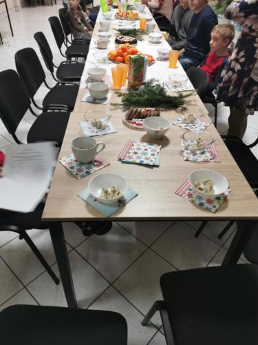Świąteczny stół, przy nim zaczynają gromadzić się uczestnicy spotkania