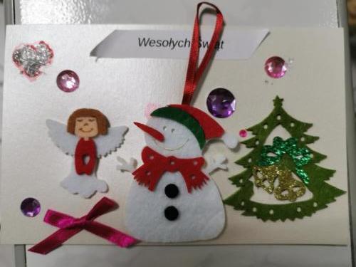 Kartka świąteczna wykonana przez dziecko, na kartce anioł, bałwan i choinka z filcu