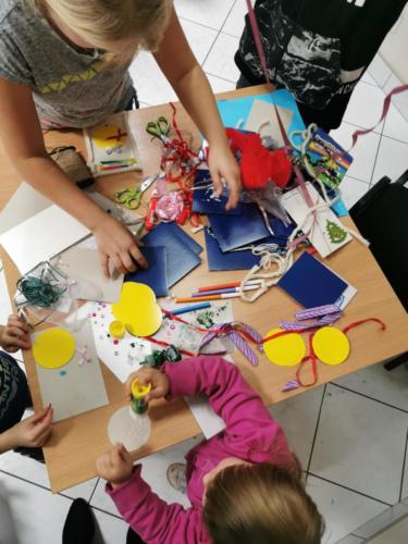 Materiały plastyczne potrzebnych do wykonania kartek świątecznych, m.in. papier, mazaki, wstążki, klej