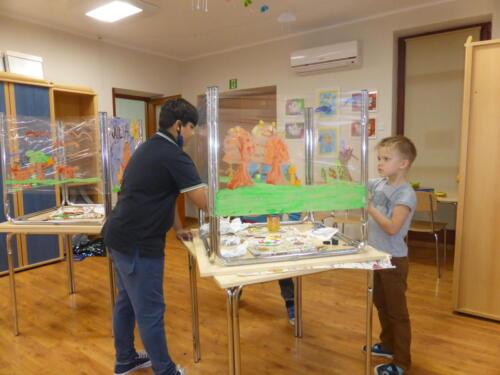 chłopcy malują na przeźroczystej folii jesienne drzewa
