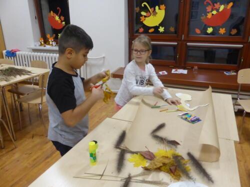 dziewczynka i chłopiec przyklejają postać Pani Jesieni na kartkę szarego papieru