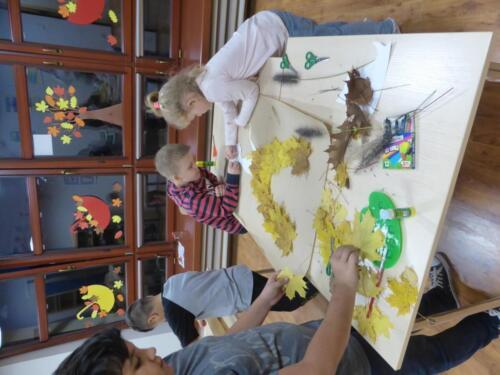 dzieci tworzą sukienkę z liści dla Pani Jesieni