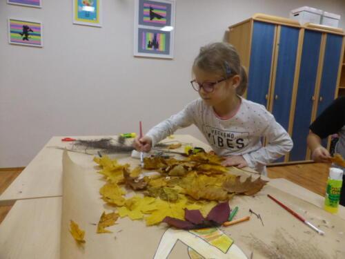 dziewczynka ozdabia liśćmi sukienkę Pani Jesieni