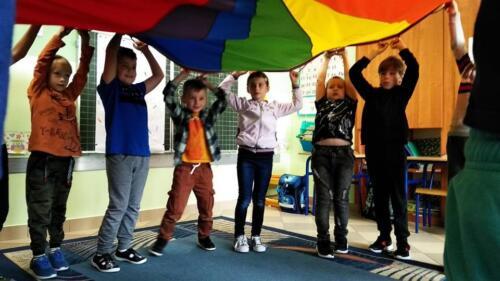 dzieci stoją w kole, nad głowami trzymają chustę Klanza