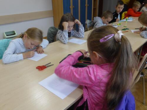 Dzieci siedzą przy długim stole i rysują