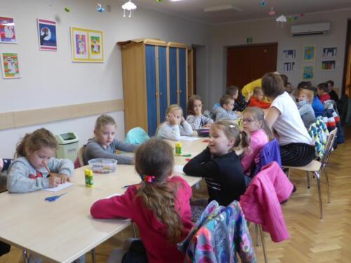 Dzieci siedzą przy długim stole, na nim nożyczki, kleje w sztyfcie i kredki