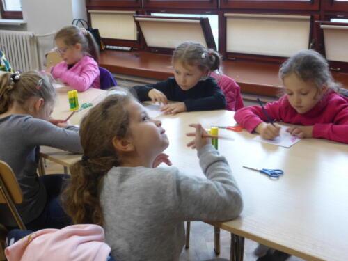 uczestnicy warsztatów siedzą przy stole i rysują