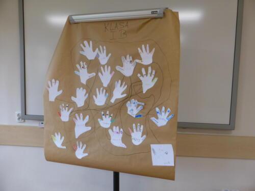 Duży arkusz szarego papieru, na nim naklejone dłonie z papieru