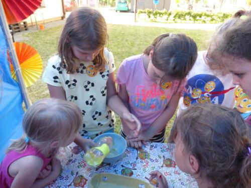 dzieci przeprowadzające eksperyment z wykorzystaniem miski i wody z butelki